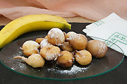 banana fritters in ball shape side view close-up from above left on oval glass dish and dark tableloth,italian food