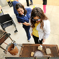 Connie Rogers, an ICC student in the Occupational Therapy Assistant program, helps Breanna Lopez, a Senior at South Pontotoc and a student in the Intro to Health Professions class through Northeast Mississippi Community College, simulate flipping burgers on a grill with no use of her right hand along with wearing glasses that sinulate peripheral vision loss during the Empathy Experience Wednesday at Longtown Medical Park in Tupelo. North Missisippi Medical Center staff as well as Certified Occupational Therapy Assistants students from ICC worked at stations to simulate what it's like to have a disability and how the Occupational Therapists help people overcome handicaps.