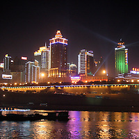 Asia, China, Chongqing.  The city of Chongqing lights up at night as cruises deaprt on the Yangtze River.