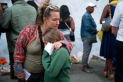 © Licensed to London News Pictures. 16/06/2017. London, UK. A woman and daughter embrace near a memorial wall  for the victims of the Grenfell tower block fire in west London. The blaze engulfed the 27-storey building killing 12 - with 34 people still in hospital, 18 of whom are in critical condition. The fire brigade say that they don't expect to find anyone else alive. Photo credit: Guilhem Baker/LNP