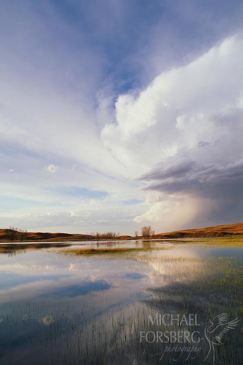 Sweeping clouds reflect in the lake below.  Nebraska Sandhills.