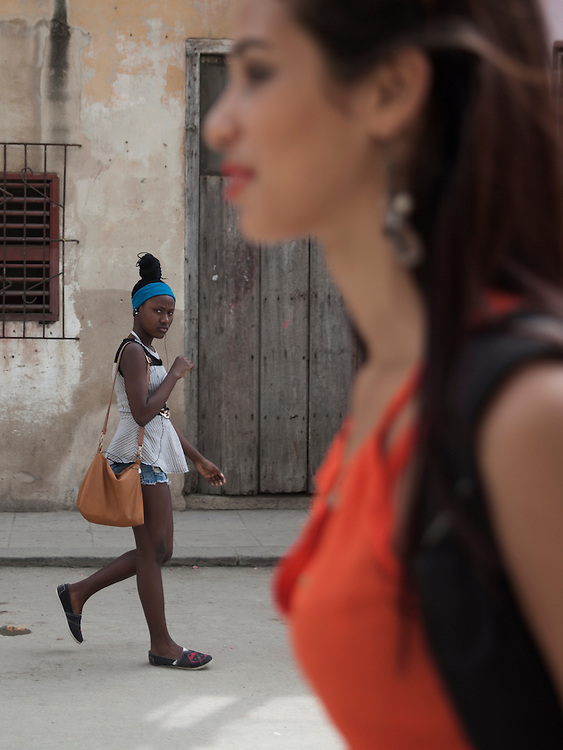 A young black woman looks at a young white woman on a street of Habana Centro, Cuba.