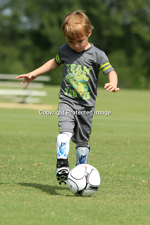 John White, 4, dribbles the ball back in as his group does a race to help with control and footwork as he attends the Tupelo Youth Soccer Association's Summer Soccer Camp Tuesday morning at Ballard Park.