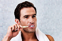 Portrait of man brushing his teeth while looking in to the mirror