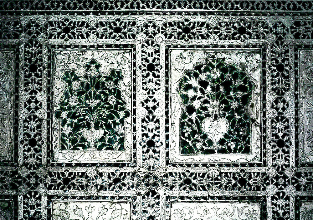 Agra, Red Fort, sheesh mahal [glass palace] wall decoration of white plaster studded with glass and mirror chips, an exhample of Mughal architectural ornament.  Its purpose was to reflect light from outside into the interior of a room, or from a candle at night.