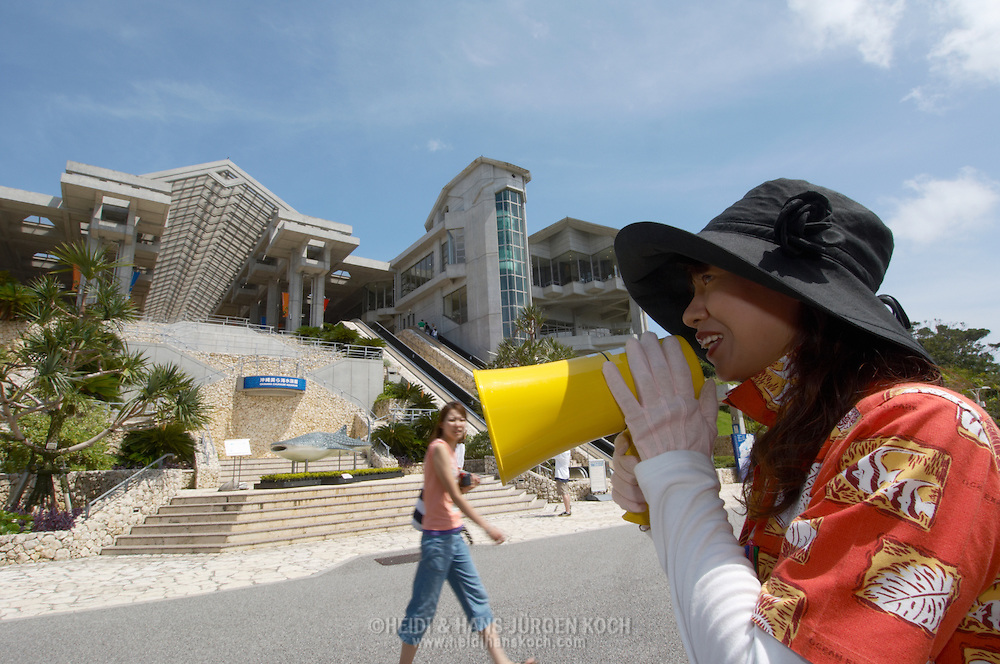 JPN, Japan: Okinawa Churaumi Aquarium, mit Hilfe eines Megaphones werden die Besucher in die richtige Richtung dirigiert, Ocean Expa Park, Okinawa, Okinawa | JPN, Japan: Okinawa Churaumi Aquarium, woman using a megaphone to directing the visitors in the right direction, Ocean Expo Park, Okinawa, Okinawa |