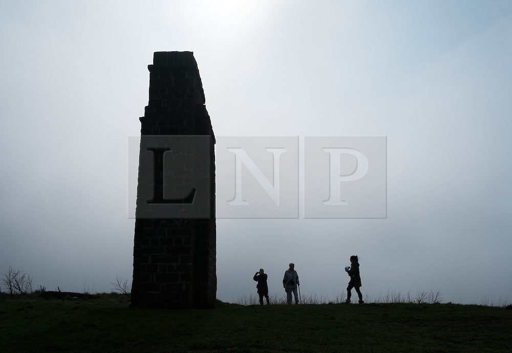 © Licensed to London News Pictures. 29/03/2014<br /> <br /> Eston Hills, Teesside, United Kingdom<br /> <br /> People stand at the base of a monument on the top of Eston Nab on Teesside. A community group called the Friends of Eston Hills have recently raised £15000 in just seven weeks to buy the land and return it to public ownership. Today they held a celebration on top of the Nab which is the rocky summit of the Eston Hills to mark the occasion.<br /> <br /> The area will now be returned to public ownership for the first time in hundreds of years and there are plans to raise more funds to create a heritage trail, clean the site up and create a memorial to 375 miners who died when there was an iron mine on the site.<br /> <br /> <br /> Photo credit : Ian Forsyth/LNP