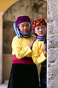 """Two little girls are curious to see """"mua khen"""" dance in the old Dong Van market, Ha Giang."""