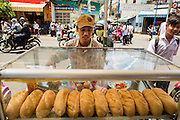 "12 APRIL 2012 - HO CHI MINH CITY, VIETNAM:  A sandwich vendor sells lunch sandwiches on a street in Cholon, the Chinese-influenced section of Ho Chi Minh City (former Saigon). It is the largest ""Chinatown"" in Vietnam. Cholon consists of the western half of District 5 as well as several adjoining neighborhoods in District 6. The Vietnamese name Cholon literally means ""big"" (lon) ""market"" (cho). Incorporated in 1879 as a city 11 km from central Saigon. By the 1930s, it had expanded to the city limit of Saigon. On April 27, 1931, French colonial authorities merged the two cities to form Saigon-Cholon. In 1956, ""Cholon"" was dropped from the name and the city became known as Saigon. During the Vietnam War (called the American War by the Vietnamese), soldiers and deserters from the United States Army maintained a thriving black market in Cholon, trading in various American and especially U.S Army-issue items.         PHOTO BY JACK KURTZ"