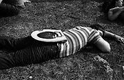 man passed out on grass with toilet set on back at a festival, U.K, 1980's.