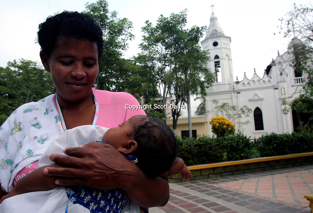 A woman holds her young baby in the plaza in front of the church in Aracataca on Monday, January 29, 2007.  Aracataca is the hometown of Garcia Marquez, the famed Colombian author most noted for his novel One Hundred Years of Solitude and also the winner of the Nobel Prize for literature. (Photo/Scott Dalton)
