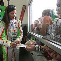 Driver Danica Patrick signs autographs in her garage area during the first practice session of the 56th Annual NASCAR Coke Zero400 race at Daytona International Speedway on Thursday, July 3, 2014 in Daytona Beach, Florida.  (AP Photo/Alex Menendez)