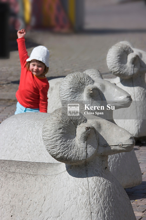Little child with sculpture of sheep, symbol of Visby, Gotland island, Sweden