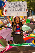 """13 JANUARY 2014 - BANGKOK, THAILAND:  An anti-government protestor holds up a sign calling for political reform during a rally in front of MBK shopping center in Bangkok. Tens of thousands of Thai anti-government protestors took to the streets of Bangkok Monday to shut down the Thai capitol. The protest was called """"Shutdown Bangkok"""" and is expected to last at least a week. The Shutdown Bangkok protest is a continuation of protests that started in early November. There have been shootings almost every night at different protests sites around Bangkok, including two Sunday night, but the protests Monday were peaceful. The malls in Bangkok stayed open Monday but many other businesses closed for the day and mass transit was swamped with both protestors and people who had to use mass transit because the roads were blocked.   PHOTO BY JACK KURTZ"""