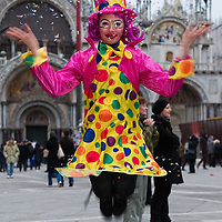 VENICE, ITALY - FEBRUARY 20:  A young woman wearing Carnival costume and mask jumps throwing confetti in front of St Mark cathedral on February 20, 2011 in Venice, Italy. The Venice Carnival, one of the largest and most important in Italy, attracts thousands of people from around the world each year. The  theme for this year's carnival is Ottocento amd Sissi, a nineteenth century evocation, and will run from February 19 till March 8.