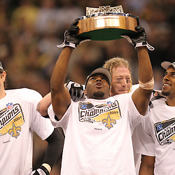 Jan 24, 2010; New Orleans, LA, USA; New Orleans Saints linebacker Jonathan Vilma (51) holds up the NFC Championship trophy following an overtime victory over the Minnesota Vikings in the 2010 NFC Championship game at the Louisiana Superdome. Mandatory Credit: Derick E. Hingle-US PRESSWIRE