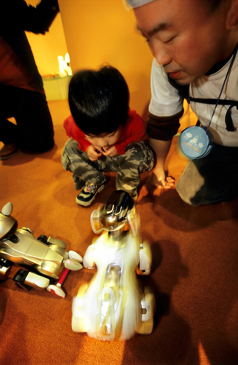 Japan, Nagoya. March/03/2007. ..A young boy and his father interact with AIBO robot pets in the Communications room of the former Nagoya Robot Museum.