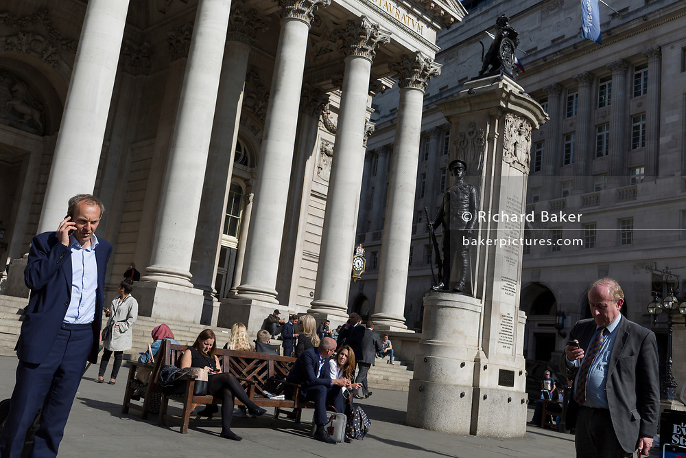 Businessmen check messages below the classical architecture of Royal Exchange and the WW1 war memorial at Bank Triangle, on 10th May 2017, in the City of London, England.