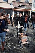 A woman pushes a dog in a pram, Jeu de Balle, Brussels.