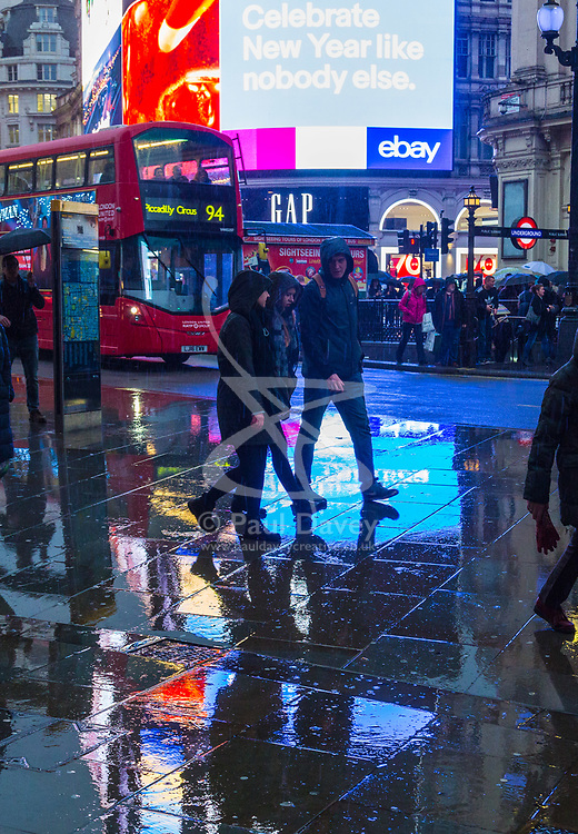 London, December 31 2017. The umbrellas come out as a downpour begins in London's west end ahead of the New Year's Eve fireworks at midnight. PICTURED: People make their way along the wet pavements of Piccadilly Circus. © SWNS