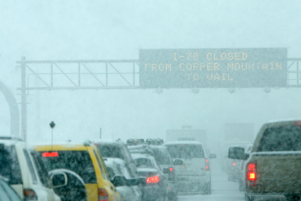 "Traffic is backed up for miles, and the overhead warning sign gives a clue as to why. ""I-70 Closed"" due to heavy snowfall."