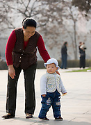 Grandmother and child play in the park by the City Wall, Xian. China has a one child policy to limit population.
