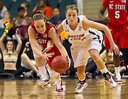 NC State's Marissa Kastanek (23) and Boston College's Kerry Shields (10) scramble for this loose ball during NC State's 71 - 70 first round victory in the 2011 ACC Women's Basketball Tournament held at the Greensboro Coluseum in Greensboro, North Carolina.  (Photo by Mark W. Sutton)