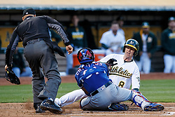 OAKLAND, CA - JUNE 14:  Jed Lowrie #8 of the Oakland Athletics is tagged out at home plate by Robinson Chirinos #61 of the Texas Rangers in front of umpire Vic Carapazza #19 during the first inning at the Oakland Coliseum on June 14, 2016 in Oakland, California. (Photo by Jason O. Watson/Getty Images) *** Local Caption *** Jed Lowrie; Robinson Chirinos; Vic Carapazza