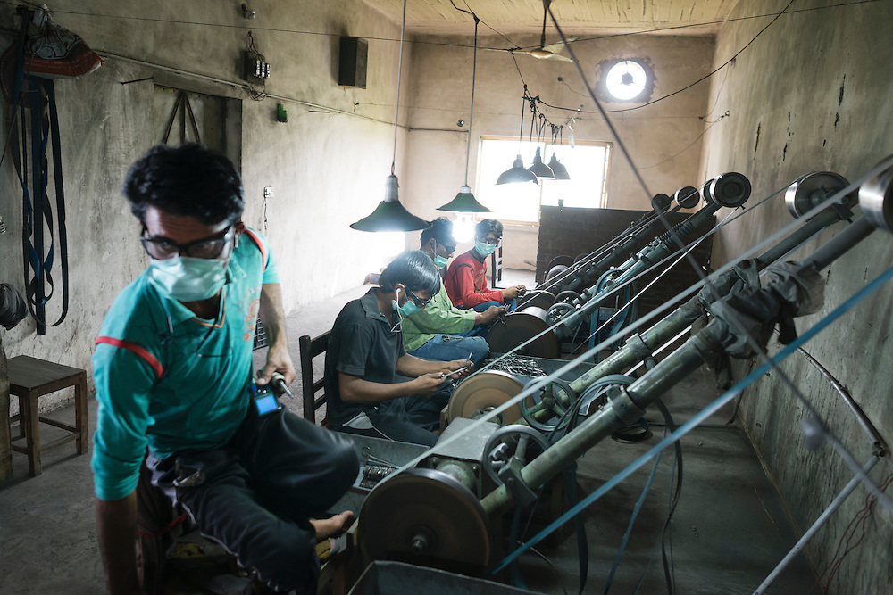 20141027 Sialkot<br /> The sound levels in the grinding rooms are deafening. And workers often only used their own earphones as sound protection. <br /> Foto: Vilhelm Stokstad / Kontinent
