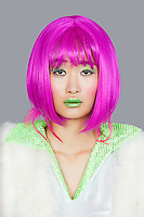 Portrait of young woman wearing pink wig over gray background