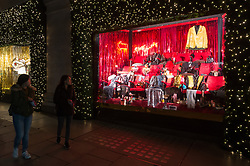 © Licensed to London News Pictures. 18/10/2018. London, UK. Two women walk past a Selfridges department store Christmas festive window display with a 'Selfridges Rocks Santa' theme. It is the first department store in the world to unveil Christmas windows. Photo credit: Ray Tang/LNP