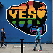 People walk by a pro-marriage equality campaign grafittu in central Dublin, Ireland.