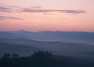 A dawn view over the misty hills of Val D'Orcia and the Belvedere.  San Quirco d'Orcia, Tuscany, Italy