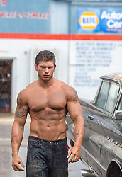 shirtless muscular man at an automotive repair shop