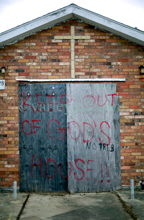 27 August 2014. Lower 9th Ward, New Orleans, Louisiana.<br /> Hurricane Katrina 9 years later. 'Keep out of the house of God' warns the graffiti sprayed on the boards covering the doors of a derelict church as the area continues to struggle to recover from Hurricane Katrina.<br /> Photo; Charlie Varley/varleypix.com