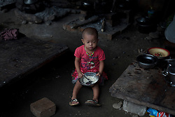 A little girl take her breakfast in Woi Chyai Internal Displacement People refugee camp in Laiza village close to the China border, Myanmar on July 16, 2012. According to KIO (Kachin Independence Organization) sources around 50000 Kachin people live as refugees in those camps.