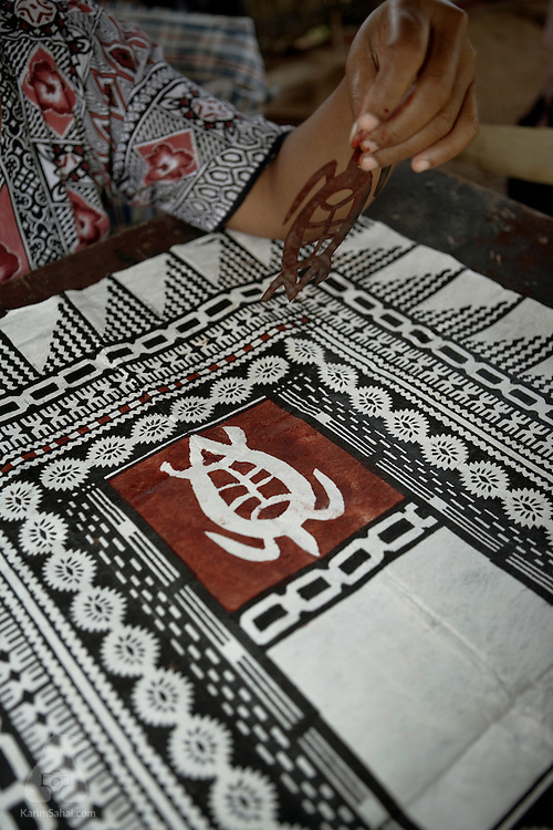 An artists paints a turtle motif on a 'tapa' cloth at the Koromakawa village, Viti Levu island, Fiji.<br /> <br /> Traditional tapa techniques use natural pigments and mulberry bark. Tapa-making is traditionally carried out by women. Tapa is an art form found in several islands of the South Pacific.