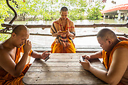 13 May 2017. Baan Kao Daeng, Thailand.<br /> Buddhist monks play computer games on their mobile telephones near to their temple in the fishing village of Baan Kao Daeng, Thailand.<br /> Photographer: Rick Findler