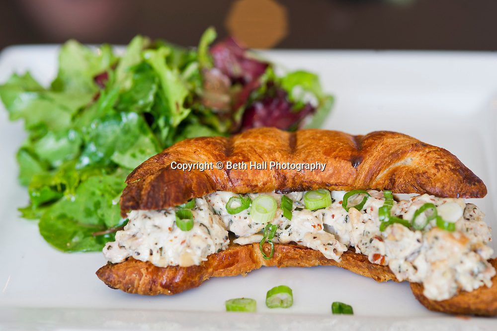 A chicken salad sandwich on a croissant served with a side salad.