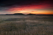 A colorful sunrise lights up the sky above a grass prairie near Dillon Pass in Badlands National Park, South Dakota. Badlands National Park contains the largest protected mixed grass prairie in the United States.