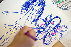 Child drawing a picture with felt tip pen at nursery school