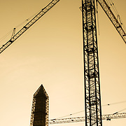 The Washington Monument covered in scaffolding and cranes nearby being used in the construction of the African American History and Culture Museum on the National Mall in Washington DC.