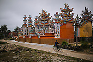 "Vietnamese man cycling near a tomb in the ""ghost city"", Hue area, Vietnam, Southeast Asia"