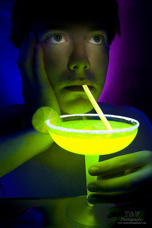 Young man drinking a margarita through a golden glowing straw.Black light