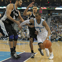 29 March 2009: New Orleans Hornets guard Chris Paul (3) drives past San Antonio Spurs defenders George Hill (3) and Tim Duncan (21) during a NBA game between Southwestern Conference rivals the New Orleans Hornets and the San Antonio Spurs at the New Orleans Arena in New Orleans, Louisiana.