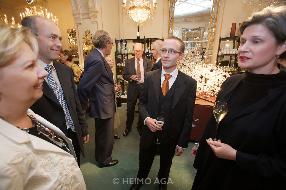 """Reception at Lobmeyr/Vienna to celebrate the restauration of 11 crystal chandeliers Lobmeyr had created for the foyer and auditorium of New York's Metropolitan Opera, in 1966..From l.: Brigitte Jank (President of Vienna's Chamber of Commerce), Andreas Rath and Johannes Rath of Lobmeyr, Elizabeth (""""Liz"""") Hurley (Director of Development, Metropolitan Opera)..The Sputnik-like steel structures with 51.000 individual crystals are completely dismantled, cleaned, and re-built from the ground, while many missing crystals and damaged or outdated parts are being replaced. This takes approximatley one month..Lobmeyr's prestigeuos client list includes H.R.H. Queen Elisabeth II., the Sultan of Brunei, Arnold Schwarzenegger and many others."""
