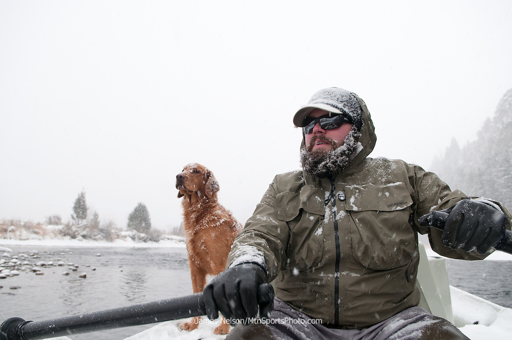 Tim Woodard, with is golden retriever Moose, rows a drift boat during a winter fly fishing trip on the South Fork of the Snake River, Idaho.