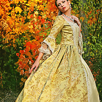 A pretty young woman in her late teens or early 20s in a beautiful regency fancy dress with colorful autumn trees