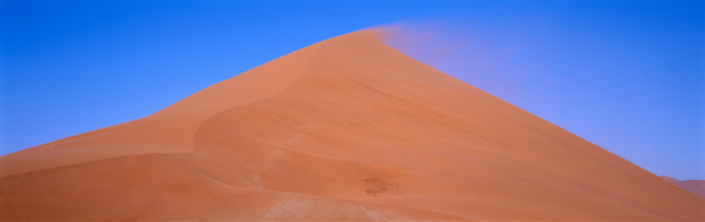 Dune with sand blowing over peak