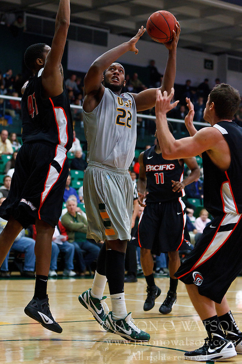 Dec 10, 2011; San Francisco CA, USA;  San Francisco Dons forward Perris Blackwell (22) shoots past Pacific Tigers center Rundell Mauge (left) during the first half at War Memorial Gym.  Mandatory Credit: Jason O. Watson-US PRESSWIRE